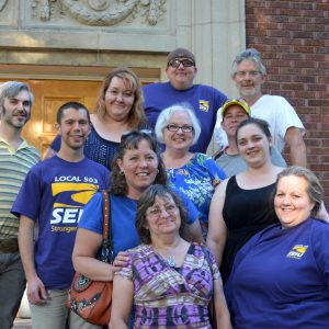 A smiling group of 11 SEIU member leaders poses for a photo on the SEIU 503 union hall steps.