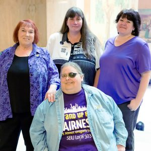 Four SEIU members stand and sit, smiling, during a visit to the Oregon State Capitol