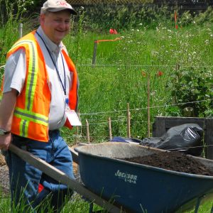 A man wearing an orange safety vest smiles as he pushes a wheel barrow full of dirt in a garden setting.