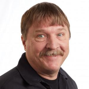 A smiling headshot portrait of SEIU member leader Craig Johnston