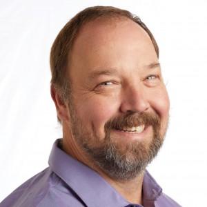 A smiling headshot portrait of SEIU member leader John Grimm