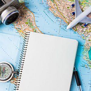 Several objects — a camera, compass, notebook, pen, and toy passenger jet — rest on a backdrop of a map.