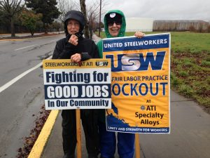 SEIU 503 retirees Nancy Greeman (left) and Catherine Stearns (right) stay active for economic justice on a windy and damp picket line standing up for Steelworkers locked out of their factory.