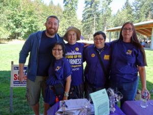 Lane Co. Labor Day: UO Higher Ed members stand with supporters at the Lane County Labor Day Picnic. From left-to-right, UO Graduate Teaching Fellows Federation member Joe Henry, UO Sublocal President Theodora Ko-Thompson, Eugene Labor Choir member Dorthy Attneave, SEIU 503 staff Marikio Yoshioka and SEIU 503 member Lauradel Collins.