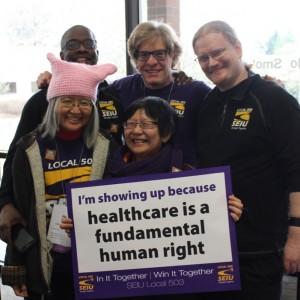 """Năm thành viên SEIU đeo cụm bánh răng SEIU cùng nhau, mỉm cười, xung quanh một tấm biển có nội dung """"Tôi xuất hiện vì chăm sóc sức khỏe là quyền cơ bản của con người""""."""