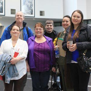 Un grupo de 6 personas sonríen, sosteniendo cafés y botellas de agua.
