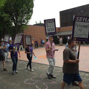 """Un piquete marchando frente a un edificio universitario. Algunos de los carteles del piquete decían """"$ 15 ahora"""", """"Jubilación con dignidad"""" y """"La justicia económica comienza a funcionar""""."""