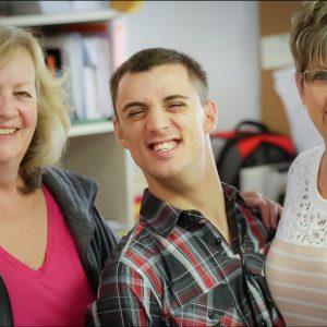 Tres personas sonríen ampliamente para la cámara.