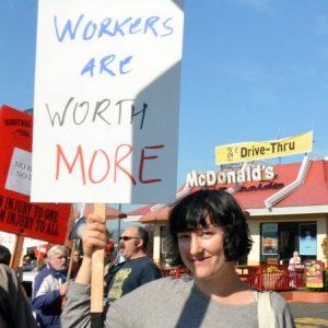 """Una persona se encuentra entre la multitud frente a un restaurante McDonald's, con un cartel que dice """"Los trabajadores valen más""""."""