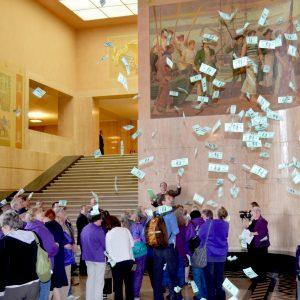 Cientos de billetes de un dólar falsos revolotean sobre un grupo de miembros de SEIU en la rotonda del Capitolio del Estado de Oregón