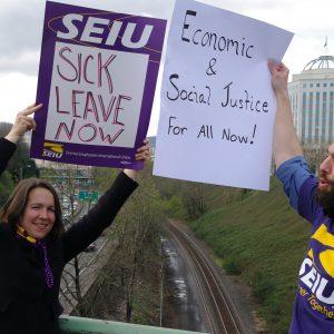 """Hai thành viên SEIU cầm biển báo khi hành động trên cầu vượt xa lộ. Các biển báo ghi """"Sick Leave Now"""" và """"Economic & Social Justice for all now!"""""""