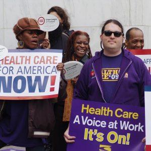 """Los miembros de SEIU se paran en una multitud de manifestaciones sosteniendo carteles, algunos dicen: """"¡Cuidado de la salud para Estados Unidos ahora!"""" y """"Cuidado de la salud. Una voz en el trabajo. ¡Está encendido!"""""""