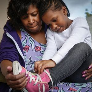 A mother helps her daughter learn to tie her shoes.