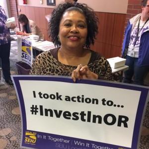 """Un miembro de SEIU sonriente sostiene un cartel que dice """"Tomé medidas para ... #InvestInOR"""""""