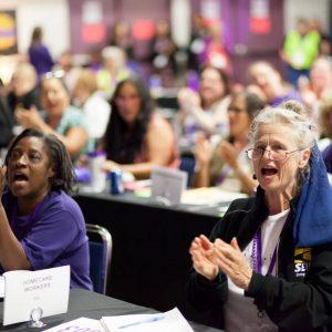 Los miembros reaccionan aplaudiendo y gritando durante una discusión del Consejo General de SEIU 503.