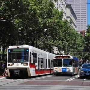 Un tren ligero TriMet MAX y un autobús uno al lado del otro en el centro de Portland