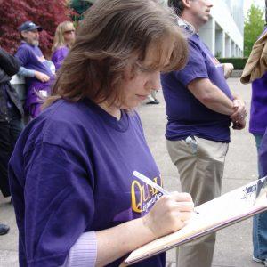 Un miembro de SEIU con una camisa morada se inscribe en un portapapeles en un mitin al aire libre.