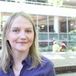 Un miembro de SEIU posa, sonriendo, fuera de un edificio de la universidad.