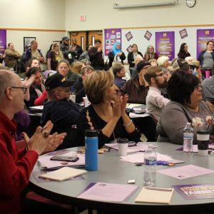 Docenas de miembros de SEIU aplauden y responden a un orador, mientras se apiñan en una sala de conferencias.