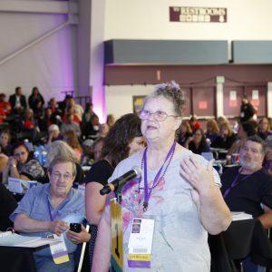 Un miembro de SEIU con cordones de color púrpura y etiquetas con su nombre está hablando frente a un micrófono de participación de la audiencia en una reunión del Concilio General. Muchos miembros se ven al fondo sentados en largas mesas negras.