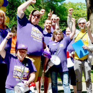 A group of 9 SEIU members, mostly wearing purple, raises their fists and smiles for the camera in a sunny park-like setting.