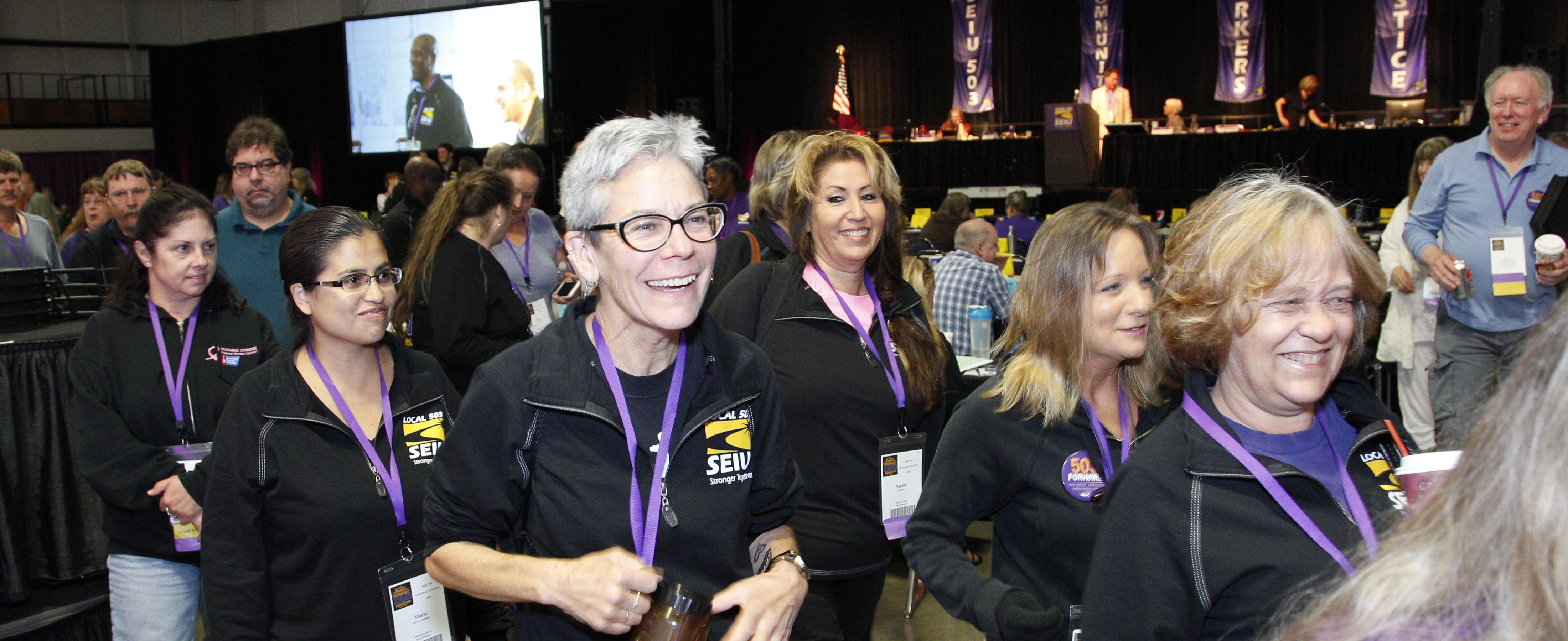 Un grupo de líderes miembros de SEIU con blusas negras y cordones morados, hace fila, sonríe y habla, durante una convención del Concilio General.
