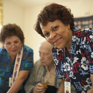 A nursing home caregiver wearing scrubs pauses to smile for the camera while she and another caregiver work with an elderly client.