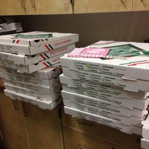 Pilas de cajas de entrega de pizzas cubren el mostrador de una oficina.