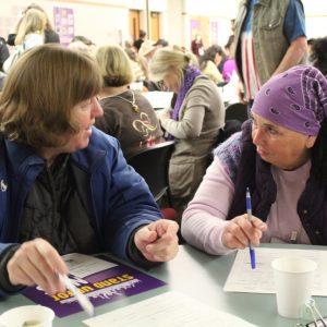 Dos miembros de SEIU entablan una conversación en una mesa circular, rodeados de docenas de otros miembros que participan en sus propias conversaciones.