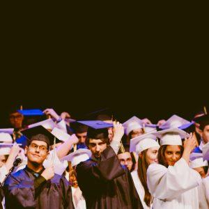 Un grupo de graduados mayores en vestidos de graduación en blanco y negro y sombreros.