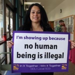 """Un miembro de SEIU sostiene un letrero que dice """"Me presento porque ningún ser humano es ilegal""""."""