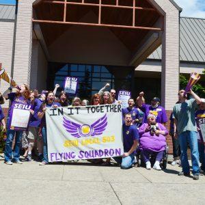 """Un grupo de miembros de SEIU se visten de púrpura, gritan y se unen, mientras sostienen una pancarta que dice """"Juntos en esto: Escuadrón Volador del Local 503 de SEIU"""""""