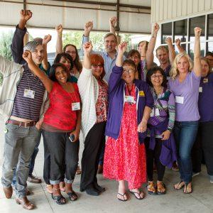 Một nhóm các lãnh đạo thành viên Hội đồng chung của SEIU 15 mỉm cười và giơ nắm tay của họ lên.