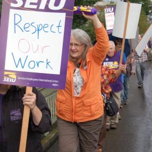 """Un piquete sindical en una calle mojada con tráfico que pasa. Una línea de miembros de SEIU llega a la distancia. La persona en primer plano sostiene un cartel que dice """"Respeta nuestro trabajo""""."""