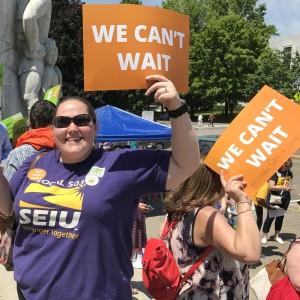 """Los miembros de SEIU sonríen y saludan a un mitin de protesta, cada uno con un cartel naranja con un texto blanco que dice """"No podemos esperar""""."""