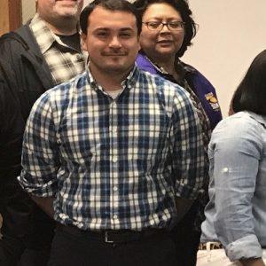El miembro de SEIU Carlos Cortes sonríe en un grupo más grande de miembros.