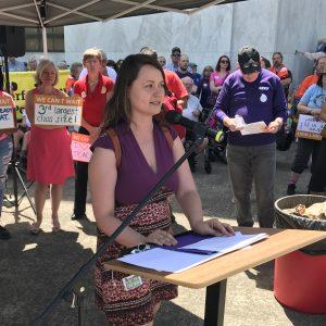 Un miembro de SEIU habla por un micrófono en un podio frente a una gran multitud reunida en los escalones del Capitolio del Estado de Oregón.