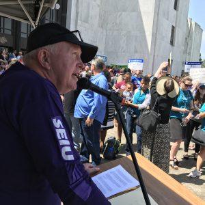El líder miembro de SEIU, Steve Demarest, habla por un micrófono ante una gran multitud de activistas sindicales en los escalones del Capitolio del Estado de Oregón.