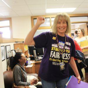 Un miembro de SEIU hace una pausa en un entorno de oficina, sonriendo y levantando el puño.