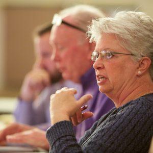Một lãnh đạo thành viên SEIU phát biểu trong một cuộc họp. Cô ấy đang tập trung, toàn thể mọi người gần hơn và xa hơn ở bàn là mờ và không tập trung.