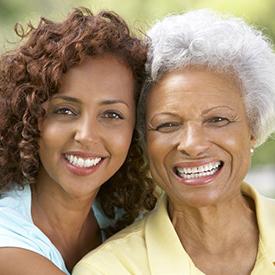 Una mujer joven y una mujer mayor posan sonriendo, con sus rostros muy juntos.