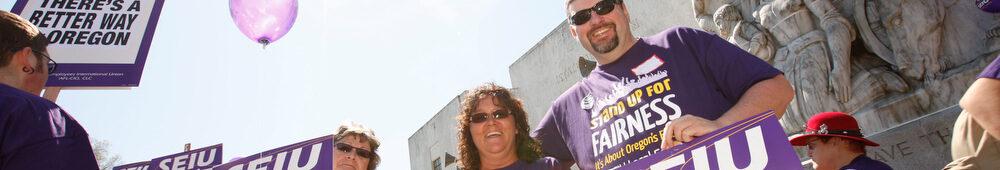"""Un grupo de miembros de SEIU vestidos de púrpura se manifiesta en el Capitolio del Estado de Oregon. Sus carteles decían """"¡Proteja a los trabajadores, mantenga buenos trabajos, ahora!"""" Hay una mejor manera para Oregon """"y"""" ¡Así es la democracia! """""""