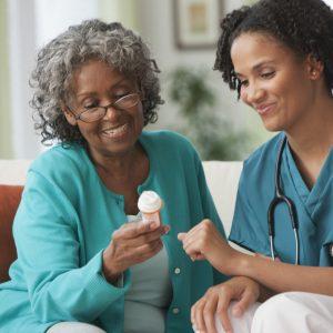 Un cuidador y un cliente anciano leen juntos la etiqueta de un frasco de medicamentos recetados.