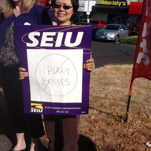 "An SEIU member stands holding a sign that reads ""Bully Bosses"" with a circle and slash through the text. She is standing with other members in front of businesses in a strip mall."