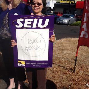 """Un miembro de SEIU está de pie sosteniendo un cartel que dice """"Bully Bosses"""" con un círculo y una barra en el texto. Ella está parada con otros miembros frente a negocios en un centro comercial."""