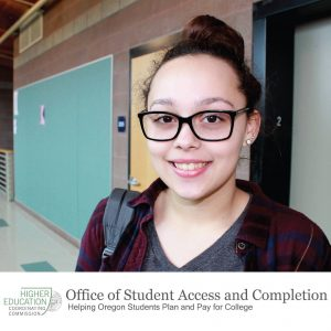 A young student smiles, standing in the hallway of a high-education institution building.