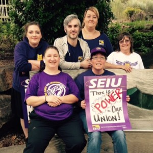 "A group of SEIU members, most with SEIU logos on their persons, sit and stand around a park bench smiling. One holds a sign that reads ""There is POWER in our UNION!"""