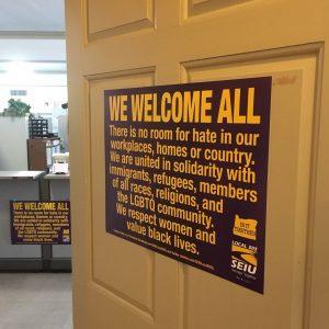 """Un letrero pegado en una puerta dice: """"DAMOS LA BIENVENIDA A TODOS No hay lugar para el odio en nuestros lugares de trabajo, hogares o país. Estamos unidos en solidaridad con los inmigrantes, refugiados, miembros de todas las razas, religiones y la comunidad LGBTQ. Respetamos mujeres y valoran la vida de los negros """"."""