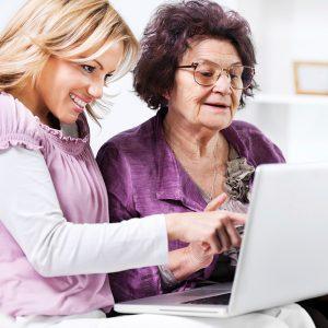 Una mujer joven le muestra a una mujer mayor algo en la pantalla de una computadora portátil. Ambas personas están sonriendo.
