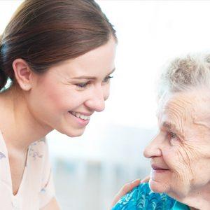 Un cuidador le sonríe a un anciano sonriente.